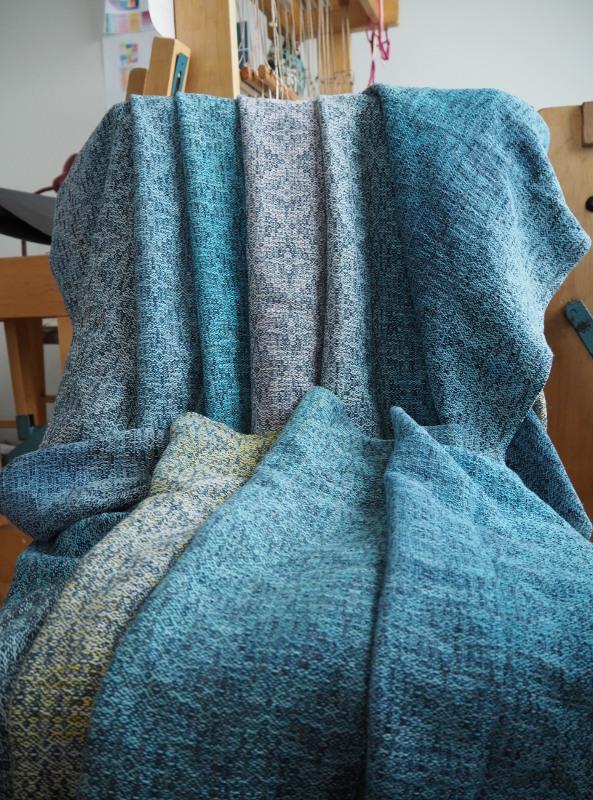 Kantoliina vekeille aseteltuna tuolilla kangaspuiden edessä